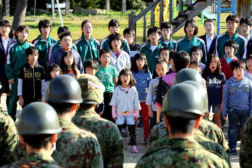 自衛隊員に感謝の歌を披露する村立王滝小中学校の子どもたち=2014年10月17日、長野県王滝村