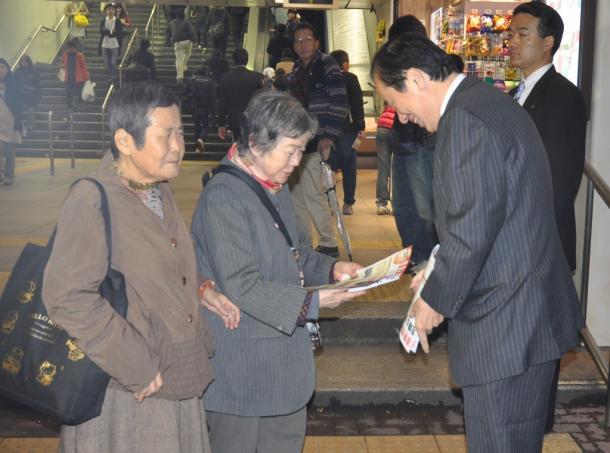 写真・図版 : JR三鷹駅北口で政策を訴えるビラを配る菅直人元首相=2014年11月21日