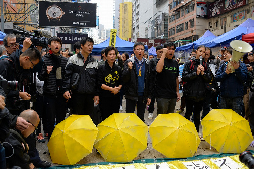 写真・図版 : 強制排除前に、最後の抗議をするデモ隊=2014年12月15日、香港・銅鑼湾