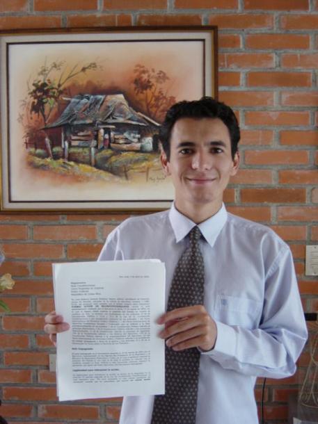 大統領への違憲訴訟で勝訴した判決文を手にする学生時代のロベルトサモラ氏2004年本人提供