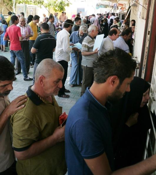 出国のための旅券取得に必要な国籍証明書を申請するために並ぶ人々=26日、バグダッドのカラダ地区で、川上泰徳撮影