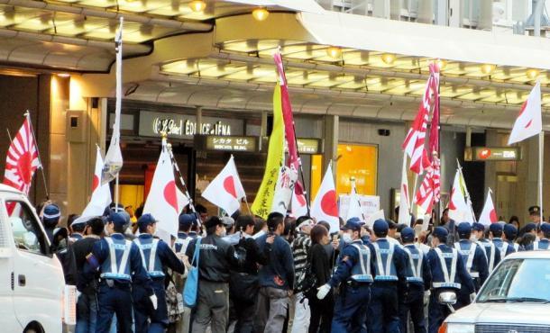 在日特権を許さない市民の会」(在特会)の街頭宣伝を「人種差別」として高額賠償を命じた10月の京都地裁判決を批判するシュプレヒコールとともに進むデモ。沿道にはデモに抗議する人たちが集まり、「帰れ」と一斉に声を上げた=京都市中京区2013112