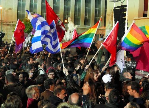写真・図版 : 急進左翼進歩連合が勝利を決め、国旗や党の旗などを振って喜びにわく支持者たち=2015年1月25日、アテネ大学本部前、梅原季哉撮影