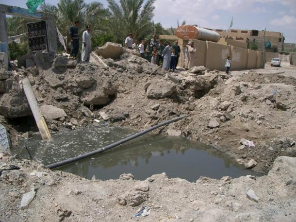 写真・図版 : 米軍の空爆によって住宅地に大きな穴があいたイラク中部ファルージャの住宅地=2004年5月、撮影・筆者