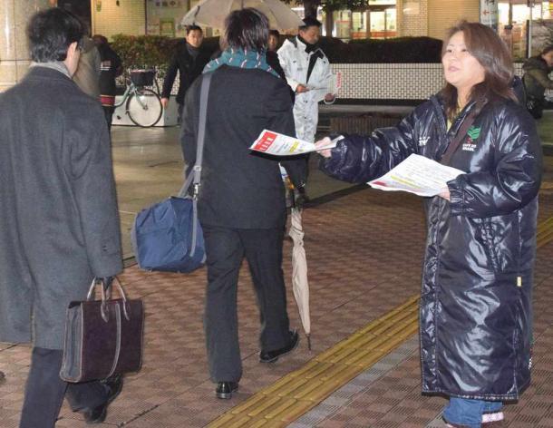 「学校にエアコンを」。駅前でチラシを配る賛成側住民=5日夕、西武線小手指駅