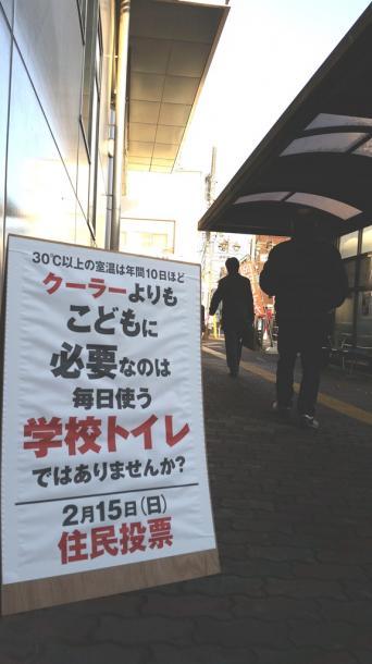 藤本正人市長は駅前で自らエアコン設置反対を訴えている。「政争の具に利用されたくない」として写真撮影は拒否した=6日早朝、西武線新所沢駅