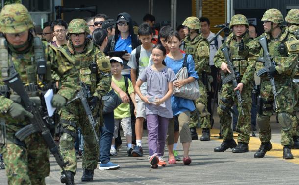 海外での「輸送訓練」で、現地を離脱する想定の在外邦人を護衛する武装した陸上自衛隊員たち=15日、タイ中部・ウタパオ海軍航空基地