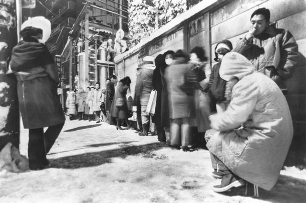 凍り付く歩道で男子中御三家と呼ばれる私立中学校の入学願書受け付けを徹夜で待つ人たち=1984年1月20日、東京都荒川区西日暮里4丁目の開成中学校