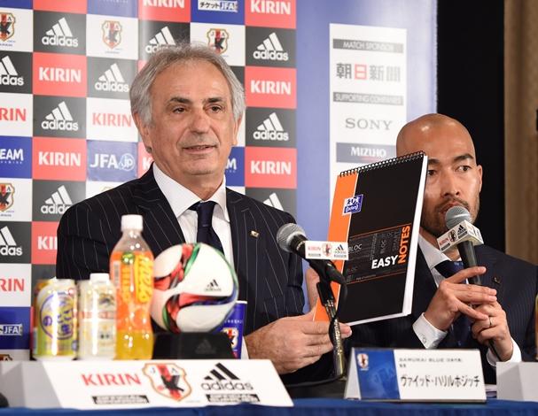ノートを手に会見するサッカー日本代表のハリルホジッチ新監督(左)=2015年3月13日、東京都港区