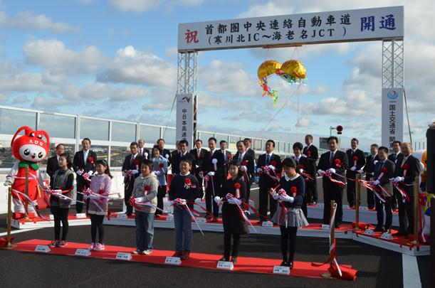 テープカットして開通を祝う地元の子どもたちや関係者=2015年3月8日、神奈川県海老名市の圏央道海老名南JCT