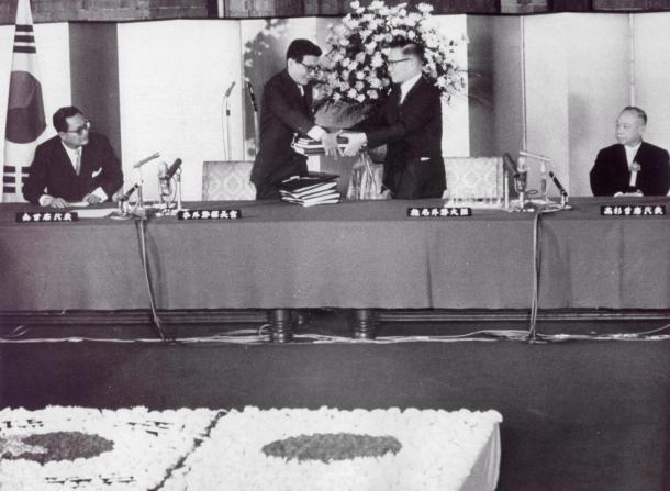 日韓基本条約の調印式が首相官邸で行われた。関係公文を交換する椎名悦三郎外相(右)と韓国の李東元(イ・ドンウォン)外務部長官