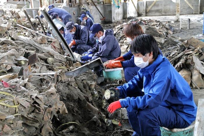 写真・図版 : 泥とがれきが流れ込んだ木の屋石巻水産の倉庫から、埋もれた缶詰を掘り起こす社員とボランティア=「缶闘記」から