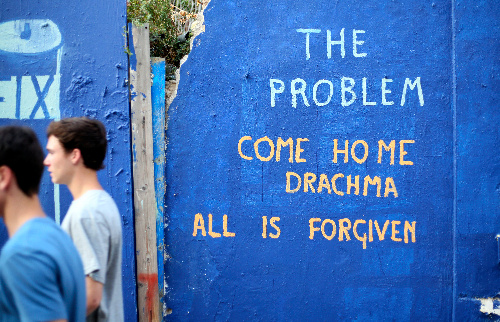 写真・図版 : プラカ地区で廃虚と化した建物の落書き。「(旧通貨の)ドラクマよ、帰って来い」=2015年7月11日午後、アテネ