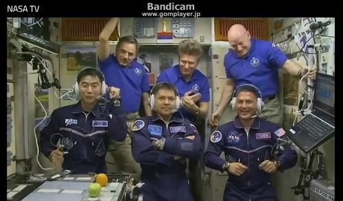 写真・図版 : 国際宇宙ステーション(ISS)に到着した油井亀美也さん=写真左。仲間の宇宙飛行士とともにカメラの前に並び、家族らと交信した=NASATVから