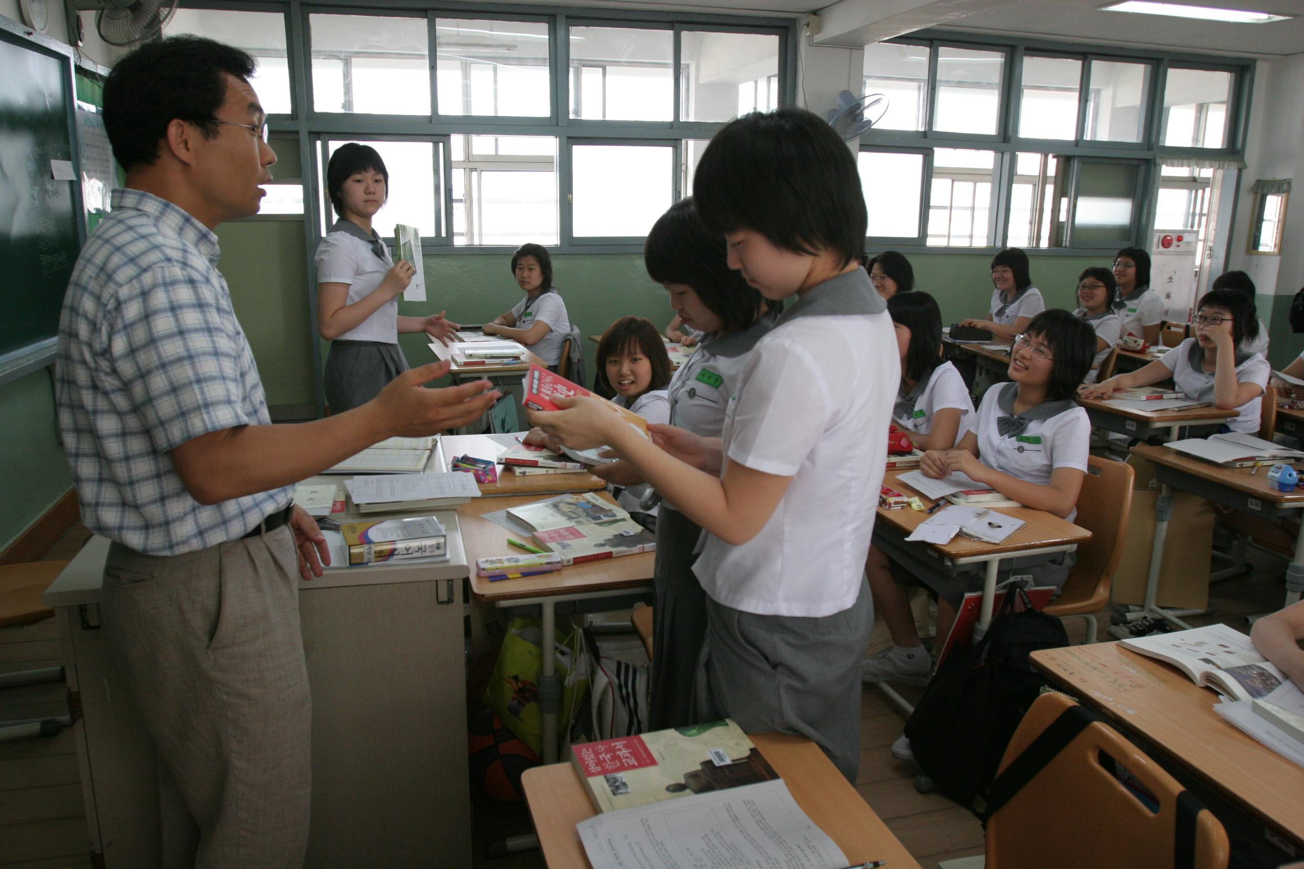 写真・図版 : 韓国・ソウル市内の金湖女子中の歴史の授業で、日・中・韓の3国で合同編集された教材が生徒たちに配られたときの様子=2005年6月14日、溝越賢撮影