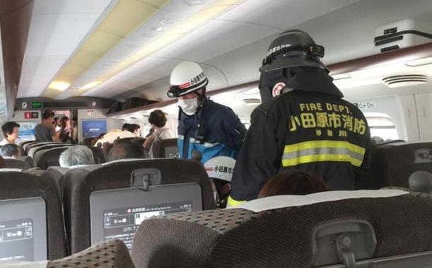 火災があった新幹線を見回る消防の職員=2015年6月30日、読者提供