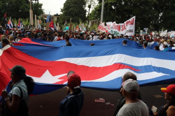 写真・図版 : 5月1日、メーデーの日のパレードとキューバ国旗。雨がどんどん強くなる=撮影・筆者