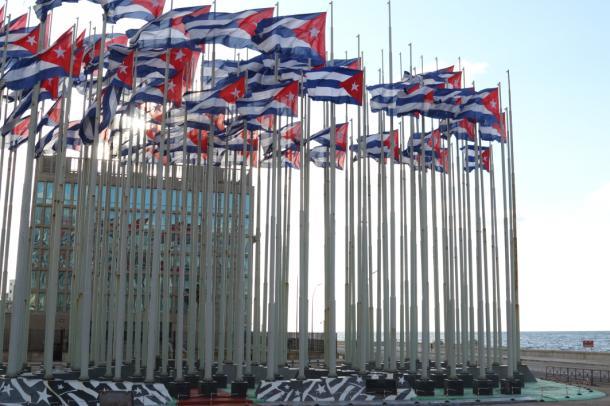 写真・図版 : 米国利益代表部前のキューバ国旗、右手はマレコン通り=撮影・筆者