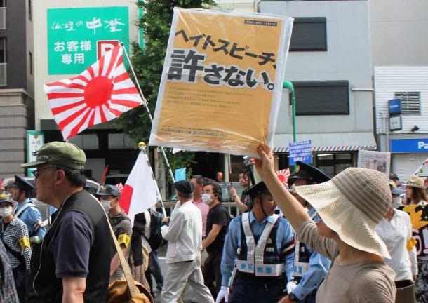 デモ参加者に向かって「ヘイトスピーチ、許さない。」のプラカードを掲げる女性=名古屋市中区