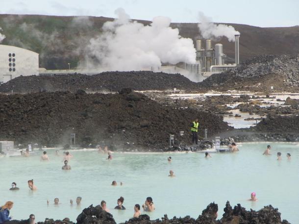 入浴客でひしめくブルー・ラグーンの向こうには地熱発電所が湯気を上げ