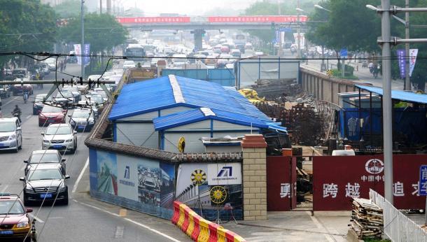 北京の地下鉄工事現場のわきを車が行き交う