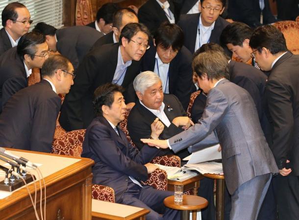 中谷元・防衛相(中央)の答弁を巡って審議が中断。対応を話し合う安倍晋三首相(左下)や与党理事ら=25日午20150825