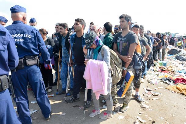 ハンガリー南部レスケで、収容施設に向かうため整列させられた難民ら。移動中にけがをし、松葉杖をつく人もいた=9月13日