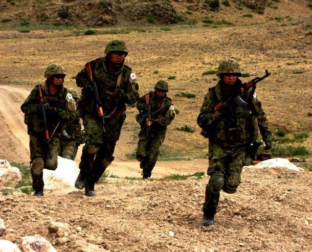 写真・図版 : 警備中に敵からの銃撃を受け、身を潜めて反撃しようと走り出す陸自隊員=2015年6月26日、モンゴル・ウランバートル郊外のモンゴル軍訓練場