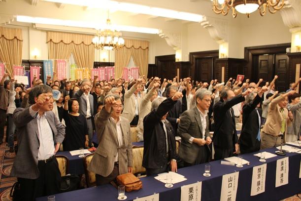 「がんばるぞ」と拳を突き上げる「安全保障関連法に反対する学者の会」の大学教員ら=2015年9月20日、東京都千代田区