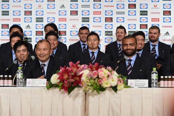 記者会見で笑顔をみせるエディ・ジョーンズヘッドコーチ(前列左)と五郎丸歩選手(中央)ら=2015年10月13日、東京都港区