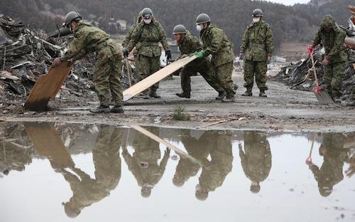 がれきを脇へ寄せて道を作る自衛隊員=2011年3月21日、宮城県南三陸町で