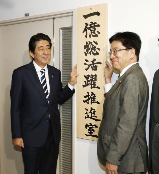 1億総活躍推進室の看板を掛け、笑顔の安倍晋三首相(左)と加藤勝信1億総活躍担当相=2015年10月