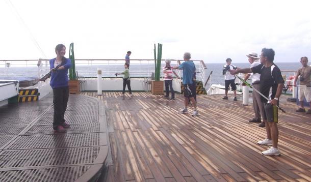 早朝、デッキでのノルディック・ウオーキングの準備体操をする人たち