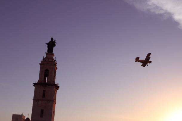 写真・図版 : 早朝、フミガシオン中の飛行機。下町の「カルメン教会」のすぐ横を飛び去る=撮影・筆者