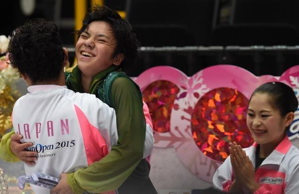 ジャパンオープンの男子フリーの演技後、村上大介(左)に抱え上げられて祝福を受ける宇野昌磨。右は宮原知子