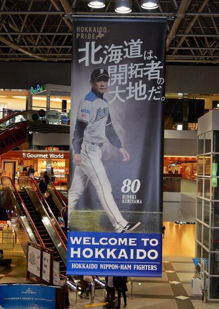 写真・図版 : 一時、新千歳空港に掲げられた北海道日本ハムファイターズの巨大広告