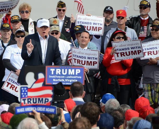 支持者に向かって演説するドナルド・トランプ氏。会場では「サイレント・マジョリティーはトランプとともに立つ」というプラカードが目立つ=10月31日、米バージニア州ノーフォーク