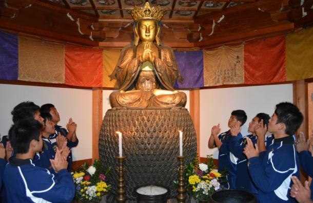 仏像と同じ「五郎丸ポーズ」をとる部員たち=岐阜県関市西日吉町 関善光寺