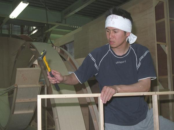 展示会ディスプレー製作・設営会社に入社し、金づちを手に作業する元サッカーJ2湘南の選手=2003年4月、埼玉県八潮市