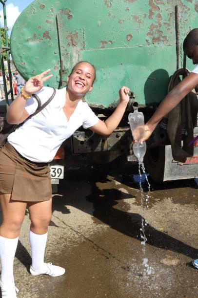 写真・図版 : 単なる水? と思いきや「聖水」を配布しているらしい。ペットボトルで持ち帰る人、顔や手を洗って浄める人=撮影・筆者