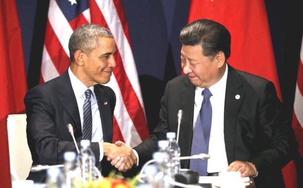 写真・図版 : 11月30日、パリでの首脳会談の際、握手するオバマ米大統領と習近平・中国国家主席=ロイター