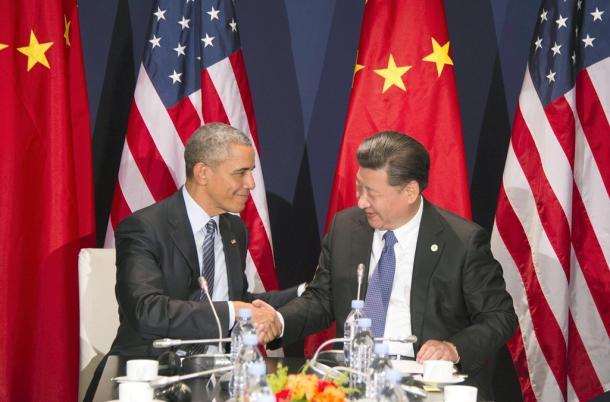 写真・図版 : パリでの国連気候変動会議(COP21)の開幕の前に開かれた11月30日の米中首脳会談で握手するオバマ米大統領(左)と、習近平・中国国家主席=AFP時事