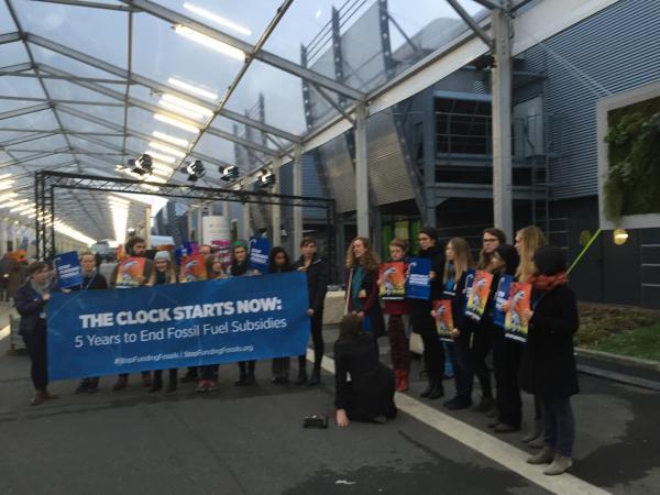 写真・図版 : COP21で化石燃料への補助金中止を訴える人たち=パリ
