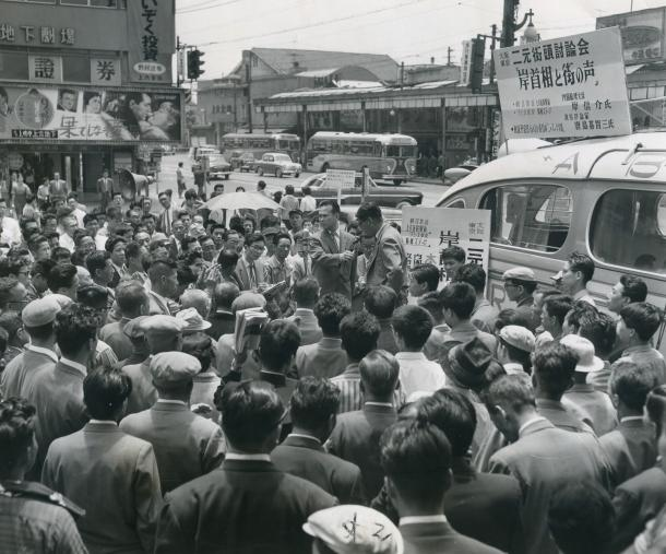 写真・図版 : 東京・大阪二元街頭討論会「岸首相と街の声」に集まった人たち。朝日放送が大阪・上六近鉄駅前、ラジオ東京が東京・新橋ステージにマイクを置き、岸信介首相と市民の声をつないだ。出演は政治評論家の唐島基智三氏