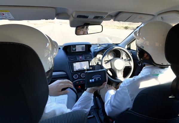 写真・図版 : 運転手がハンドルから手を離し自動運転するテスト車=2014年5月27日、北海道帯広市