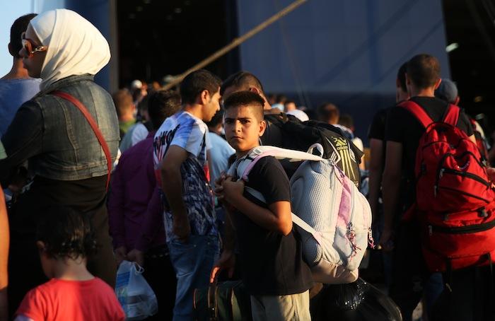 ギリシャ・レスボス島からアテネ近郊ピレウス港行きのフェリーに乗り込むシリア難民=15年7月