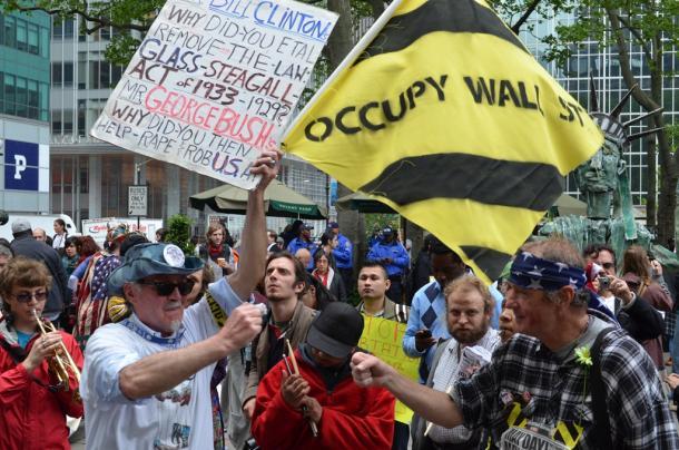 写真・図版 : 「ウォール街を占拠せよ」との旗を掲げ、口々に経済格差是正を主張するデモの参加者たち=2012年5月、ニューヨーク
