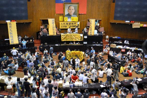 突入翌日の立法院。「国父」孫文の肖像画を飾る議場には、「馬英九が戒厳令を復活させた」「人民の生存権益を踏みにじった」などと書かれた黄色の垂れ幕が掲げられた=2014年3月19日、台北