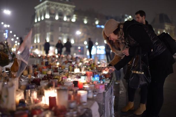 テロの犠牲者を追悼するため、ろうそくに火をつける人たち=2015年12月13日、フランス・パリ