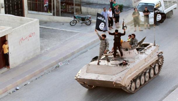 過激派組織「イスラム国」(IS)の旗を掲げてパレードするイスラム戦闘員=ロイター